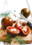 Whole, cut tomatoes and garlic in cutting board Stock Photography