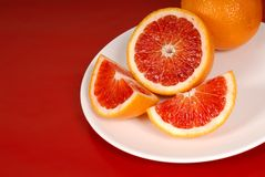 Whole and cut up blood oranges on white plate royalty free stock images
