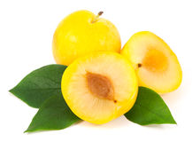 Whole and cut yellow plums with leaves Royalty Free Stock Images