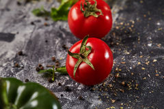 Whole and cutted tomato of pizza on italian black paper table. Whole and cutted tomato in ingredients of pizza on italian black paper table Stock Image