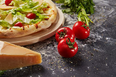Whole and cutted tomato of pizza on italian black paper table. Whole and cutted tomato in ingredients of pizza on italian black paper table Stock Images