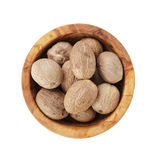 Whole dried nutmegs in bowl Stock Photos
