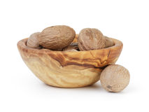 Whole dried nutmegs in bowl Stock Images