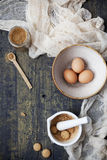 Whole eggs on bowl, cane sugar on jar and crumbled biscuits in a mortar with pestle on table with cloth Stock Photography
