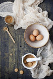 Whole eggs on bowl, cane sugar on jar and crumbled biscuits in a mortar with pestle Stock Image