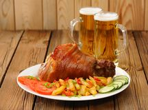 Whole Eisbein with beer, french fries, cucumbers and tomatoes Stock Photo