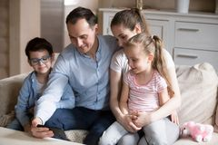Whole family watching funny video on smartphone at home royalty free stock images