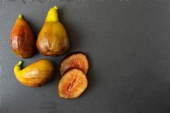 Whole figs and fig sliced on black stone plate. Top view stock images