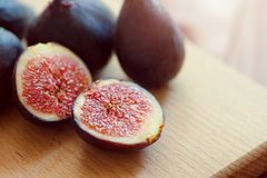 Whole figs and one fig sliced in half on top of a teak garden table. Focus is on the sliced fig. Stock Images
