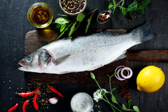 Whole Fish on Wooden Board with Herbs and Spices Royalty Free Stock Images