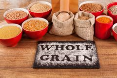 Whole food concept with whole grains and a tabletop mill. Whole food concept with various whole grains and a tabletop mill stock image