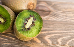 Whole Food Fruit Green Kiwi Halves Seeds Cutting Board. Two Kiwi Fruits sit on the cutting board on cut in half royalty free stock photography