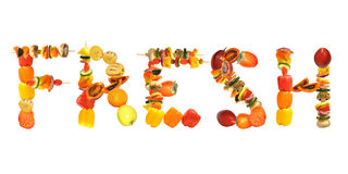 Whole foods consisting of fruits and vegetables arranged to spell the word fresh Stock Photos