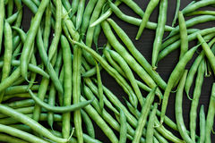 Whole French green string beans  on black rustic surface. Royalty Free Stock Images