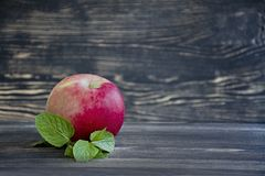 Whole fresh apples with mint on wooden background royalty free stock photo