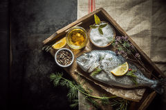 Whole fresh fish and cooking ingredients. For basting and marinating laid out on an old wooden kitchen tray on a slate counter, view from above Stock Photos