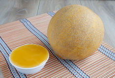 The whole fresh melon with grooves and honey into a bowl Stock Photos
