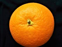 A whole fresh Orange fruit isolated on dark. It was photographed from above Stock Photography