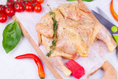 Whole fresh raw chicken prepared for roast with thyme, basil and tomatoes cherry.  Stock Image