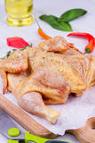 Whole fresh raw chicken prepared for roast with thyme, basil and tomatoes cherry.  Royalty Free Stock Photography