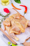 Whole fresh raw chicken prepared for roast with thyme, basil and tomatoes cherry Stock Image