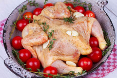 Whole fresh raw chicken prepared for roast with thyme and tomatoes cherry. Stock Images