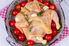 Whole fresh raw chicken prepared for roast with thyme and tomatoes cherry. Whole fresh raw chicken prepared for roast with thyme and tomatoes cherry Royalty Free Stock Photography