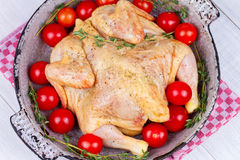 Whole fresh raw chicken prepared for roast with thyme and tomatoes cherry. Whole fresh raw chicken prepared for roast with thyme and tomatoes cherry Royalty Free Stock Images