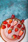Whole fresh red strawberries and sliced strawberries on wooden skewers in ceramic plate. Berries top view concept Stock Image