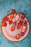 Whole fresh red strawberries and sliced strawberries on wooden skewers in ceramic plate. Berries top view concept Royalty Free Stock Photos