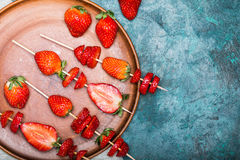 Whole fresh red strawberries and sliced strawberries on wooden skewers in ceramic plate. Berries top view concept Stock Images