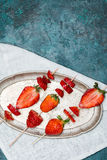 Whole fresh red strawberries and sliced strawberries on wooden skewers on vintage plate Stock Photos