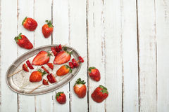 Whole fresh red strawberries and sliced strawberries on wooden skewers in vintage plate on wooden tabletop Stock Photo
