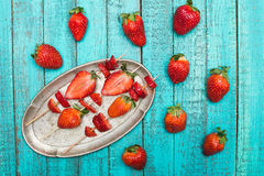 Whole fresh red strawberries and sliced strawberries on wooden skewers in vintage plate on wooden tabletop Stock Image