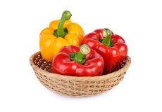 Whole fresh red and yellow bell pepper with stem in basket and o Royalty Free Stock Photos