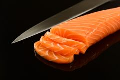 Fresh salmon isolated on black background. Whole fresh salmon fillet on mirrored black background Stock Photos