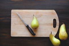 Whole fresh sweet ripe yellow and green pears, kitchen knife and cutting Board on brown wooden table background stock photo