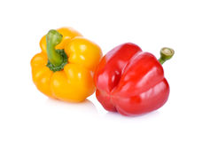 Whole fresh yellow and red bell pepper with stem on white backgr Royalty Free Stock Photos