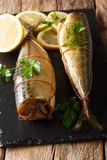 Whole freshly smoked mackerel served with lemons and parsley closeup on a slate board on the table. vertical royalty free stock image