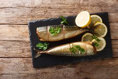 Whole freshly smoked mackerel served with lemons and parsley closeup on a slate board on the table. horizontal top view stock image