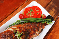Whole fried bass on plate over wood Stock Images