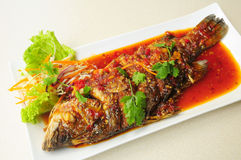 Whole fried fish topped with sweet chili sauce. Thai food, whole fried fish with sweet chili sauce Royalty Free Stock Image