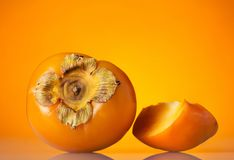 Whole fruit of persimmon and cut piece, on orange background. Whole fruit of persimmon and cut piece, on bright orange background Royalty Free Stock Image