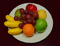 Whole Fruit Platter on White Plate on Wooden Table. Preparing to be served. This beautiful arrangement can be used as both decoration and welcome gift Stock Photo