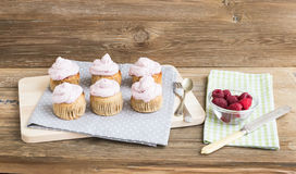 Whole garin cupcakes with cheese cream and fresh raspberries. Over a rough wooden background Stock Image