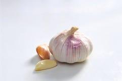 Whole Garlic. Whole white garlic with two extra peeled segments beside Stock Photo