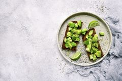 Whole grain avocado toasts with olive oil.Top view with copy spa. Whole grain avocado toasts with olive oil on a craft plate over light slate,stone or concrete Stock Photography