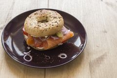 Whole Grain Bagel with salmon, cream cheese, onions and kosher pickle. A whole grain bagel topped with salmon, cream cheese, onions and kosher pickle served on a Royalty Free Stock Images