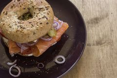 Whole Grain Bagel with salmon, cream cheese, onions and kosher pickle. A whole grain bagel topped with salmon, cream cheese, onions and kosher pickle served on a Stock Photography