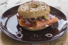 Whole Grain Bagel with salmon, cream cheese, onions and kosher pickle. A whole grain bagel topped with salmon, cream cheese, onions and kosher pickle served on a Stock Photos